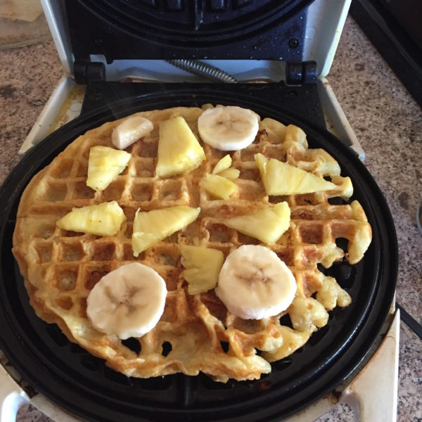 Just place the pineapple and bananas on the waffle when it is halfway finished with the cooking process...then sprinkle on a little brown sugar so it caramelizes.